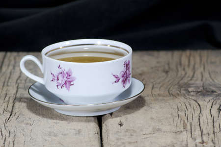 The tea in a beautiful white floral tea cup is placed on an old wooden table