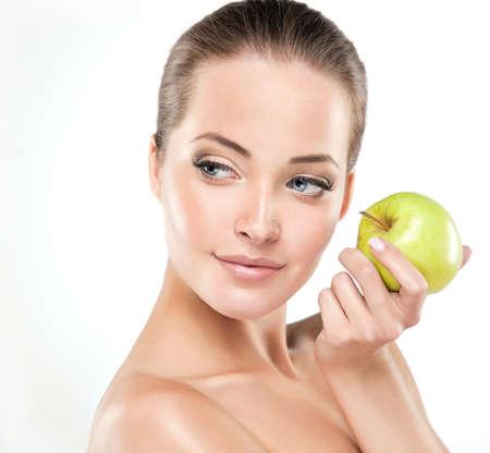 어린 소녀는 녹색 사과 들고 미소. 건강 및 미용 스톡 콘텐츠