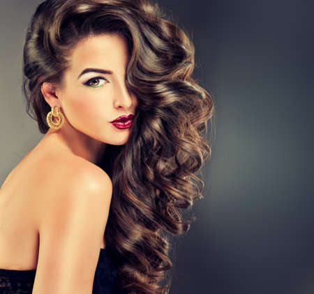 woman long hair: Beautiful model brunette with long curled hair
