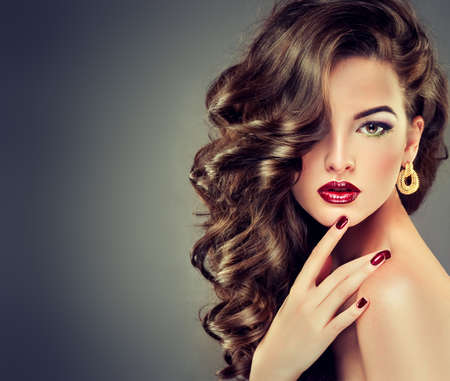 Beautiful model brunette with long curled hair photo