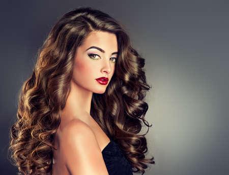 aretes: Bella modelo morena con el pelo rizado largo Foto de archivo