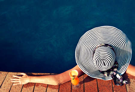 drink at the beach: A girl in a summer hat in the pool. Stock Photo