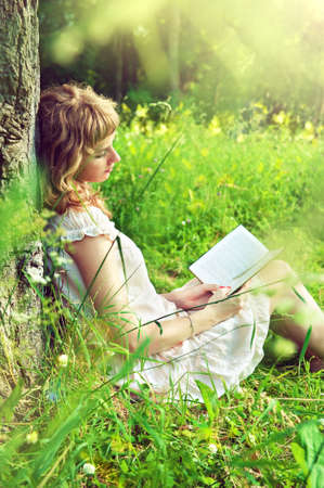 girl reading a book under a tree in nature photo