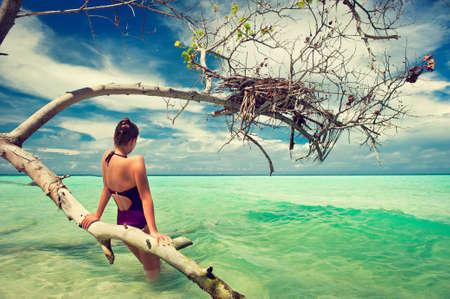 cielo y mar: Una chica joven que se reclina cerca de un �rbol en el mar turquesa