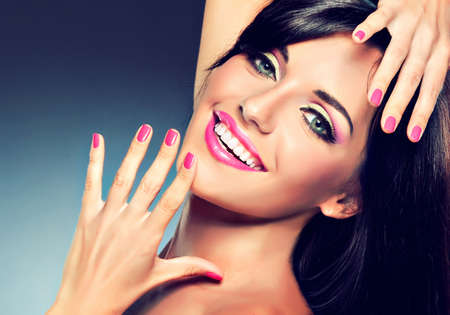model girl with a beautiful smile and fuchsia color manicure