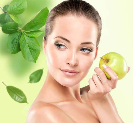 Chica joven sonriente que sostiene una manzana verde. Salud y belleza