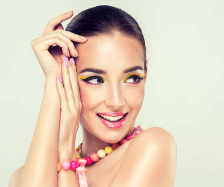 spring fashion: Girl model with bright make-up and coloured nail