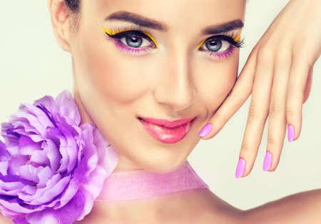 Buena chica con brillante maquillaje y flor violeta Foto de archivo - 37616406