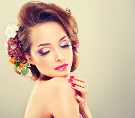 cabello rizado: Frescura de primavera. Chica con flores en colores pastel delicados en el pelo rizado Foto de archivo