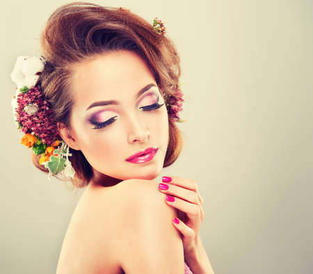 Spring freshness. Girl with delicate pastel flowers in curly hair Stock Photo