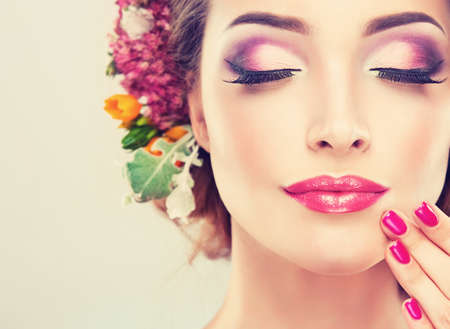 leuchtend: Frühlingsfrische. Mädchen mit zarten Pastellblumen im lockigen Haar Lizenzfreie Bilder