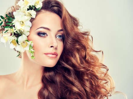 Spring freshness. Girl with delicate pastel flowers in curly hair 스톡 콘텐츠