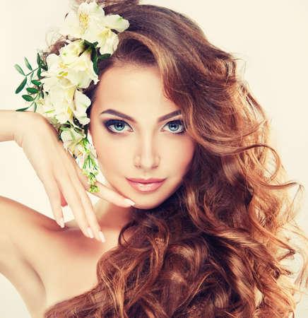 Frühlingsfrische. Mädchen mit zarten Pastellblumen im lockigen Haar Standard-Bild