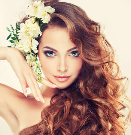 Spring freshness. Girl with delicate pastel flowers in curly hair Banco de Imagens