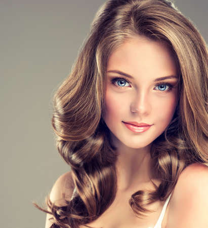 champu: Sonrisa hermosa chica, cabello castaño con un peinado elegante, onda del pelo, rizado Foto de archivo