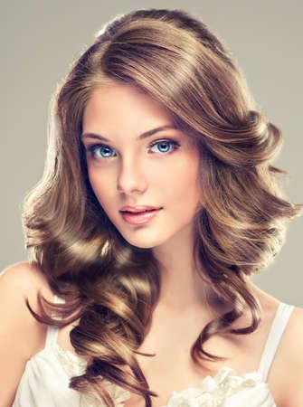cabello rizado: Sonrisa hermosa chica, cabello casta�o con un peinado elegante, onda del pelo, rizado Foto de archivo