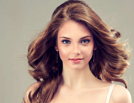 colours: Smiling Beautiful girl, brown hair with an elegant hairstyle , hair wave ,curly