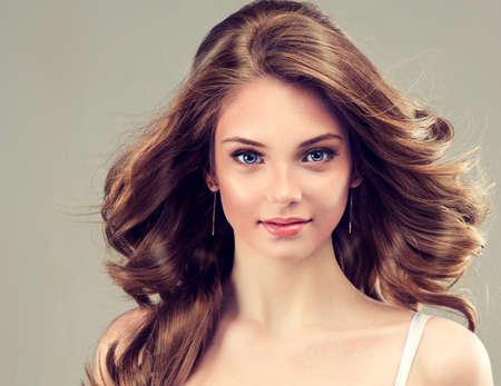 aretes: Sonrisa hermosa chica, cabello castaño con un peinado elegante, onda del pelo, rizado Foto de archivo