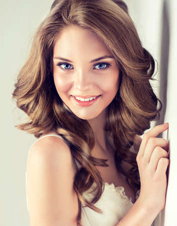 curly: Smiling Beautiful girl, brown hair with an elegant hairstyle , hair wave ,curly