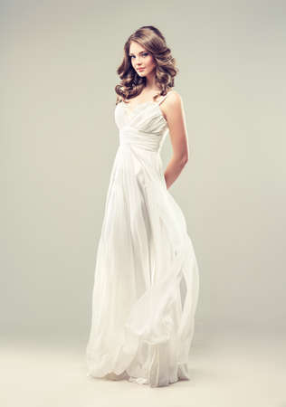 Girl model in a white wedding dress with elegant hairstyle