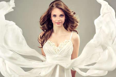 aretes: Modelo de la muchacha en un vestido de novia blanco con el peinado elegante Foto de archivo