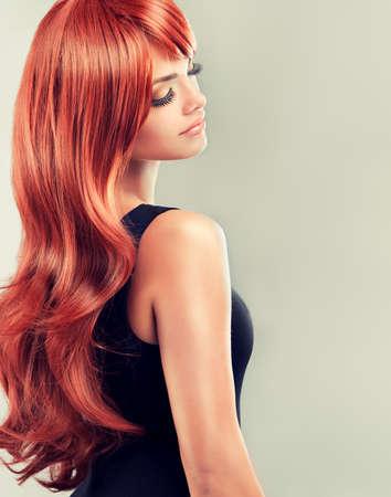 美しい光沢のある赤い髪とファッションの女の子。長い巻き毛の赤い髪をモデルします。