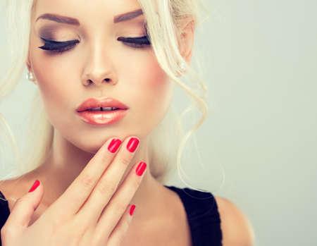 レトロ スタイルふっく髪とふさふさした尾を持つ美しいモデル。赤い爪マニキュア