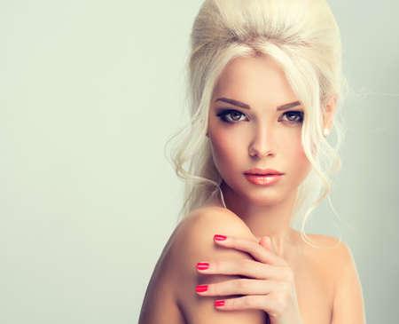 unas largas: Modelo hermoso con el estilo retro del pelo del pelo cardado y una cola espesa. Clavos rojos manicura Foto de archivo