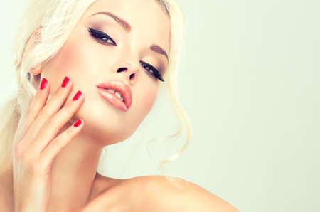 maquillaje de ojos: Modelo hermoso con el estilo retro del pelo del pelo cardado y una cola espesa. Clavos rojos manicura Foto de archivo