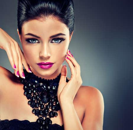 Modèle avec la mode des ongles fuchsia polonais et collier noir