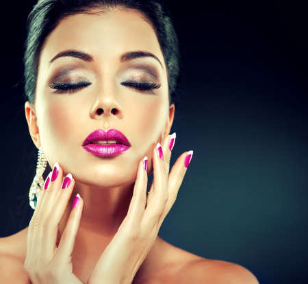 red nail: Model with trendy makeup Smokey eyes fuchsia lips and nails.