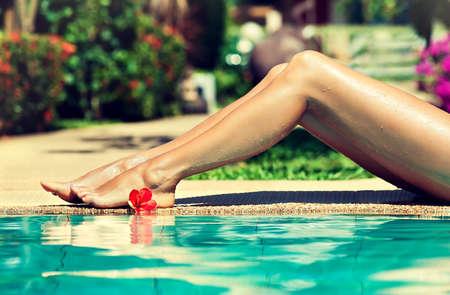 depilacion con cera: bonitas piernas de la mujer cerca de la piscina Foto de archivo