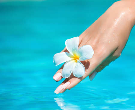 Graceful woman hand touching pure water. Hand care.