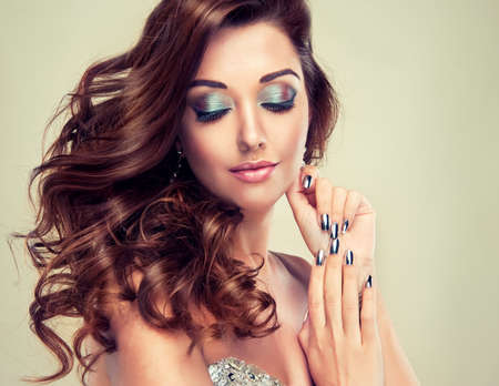 Beautiful model with long curly hair fashion makeup and silver nails 写真素材
