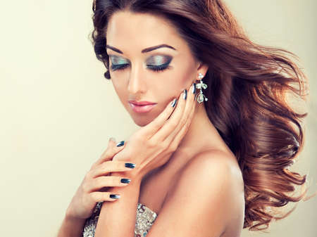 Beautiful model with long curly hair fashion makeup and silver nails photo