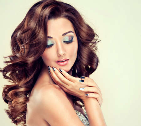 Beautiful model with long curly hair fashion makeup and silver nails Stock Photo