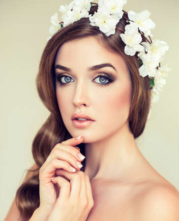 Spring freshness. Girl with delicate pastel flowers in hair wreath of white flowers photo