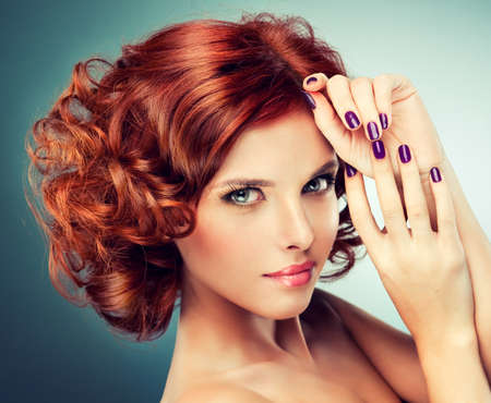 red nail colour: pretty redhaired girl with curls and fashionable makeup