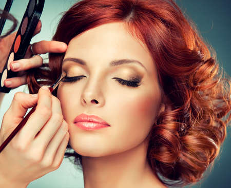 pretty redhaired girl with curls.makeup in process Banco de Imagens