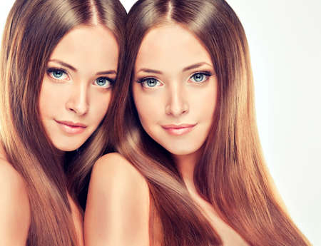 Beautiful young and fresh girl twins with long shiny healthy hair photo
