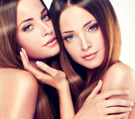 twins: Beautiful young and fresh girl twins with long shiny healthy hair