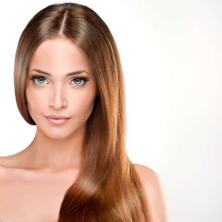 Belle fille avec les cheveux bruns. Longue service de cheveux raides avec la santé.