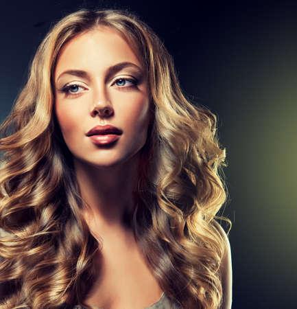 美しいカールと光沢のある茶色の髪とファッションの女の子