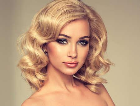 Charming girl blonde curly hair. Beautiful fashion model.