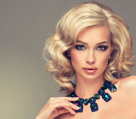 Beautiful cute girl with blonde curly hair with a necklace of precious stones Standard-Bild