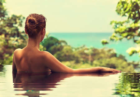 spa resort: Beautiful girl rests near the swimming pool, sunbathing. Spa treatments. Stock Photo