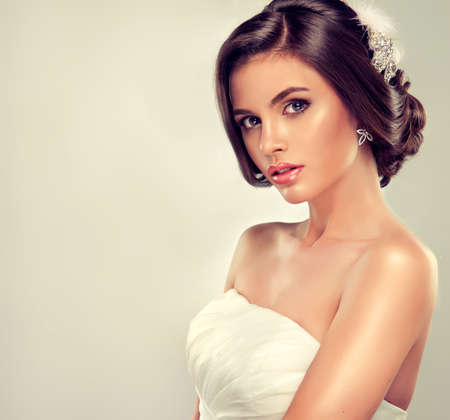 up skirt: Girl bride in wedding dress with elegant hairstyle. Stock Photo