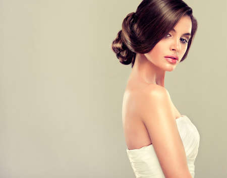 woman dress: Girl bride in wedding dress with elegant hairstyle. Stock Photo