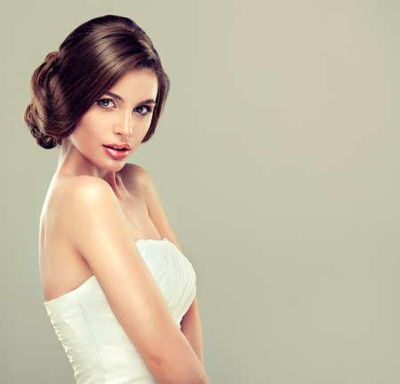 modelos posando: Chica de la novia en vestido de novia con el peinado elegante. Foto de archivo