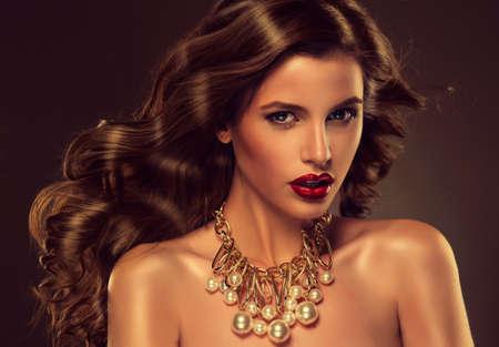 Modelo de la muchacha hermosa con el pelo largo y castaño encrespado con el collar grande Foto de archivo